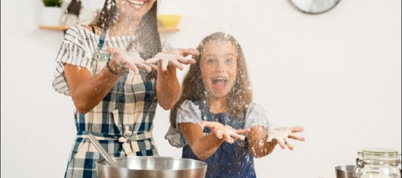 Mother and daughter throwing flour